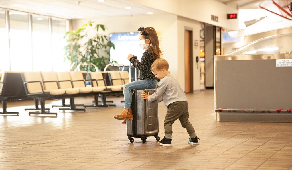 boy pushing girl on luggage through airport